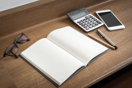appointment book: The notebook is spread out on a wooden desk.