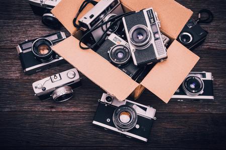 illustrative editorial: BANGKOK,THAILAND - JUNE 19,2017 : Retro film cameras on wooden background.