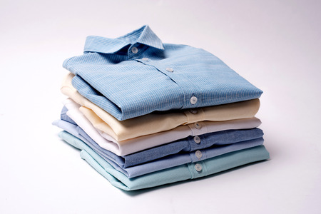 Classic men's shirts stacked on white background 写真素材
