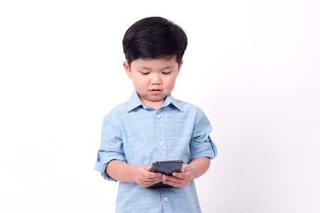 boy playing mobile phone on white background. Stockfoto