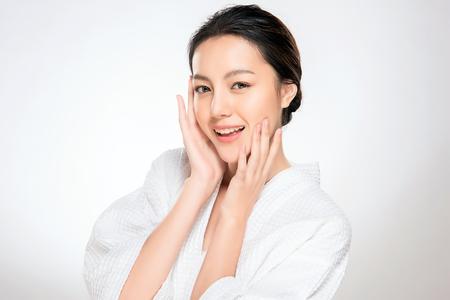 Piękna młoda azjatykcia kobieta z czystym, świeżym wyglądem skóry. Pielęgnacja twarzy dziewczyny. Zabieg na twarz. Kosmetologia, uroda i spa.