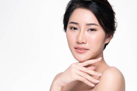 Piękna młoda Azjatycka kobieta z czystą, świeżą skórą dotyka własnej twarzy, zabiegi na twarz, kosmetologia, uroda i spa,