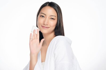 Happy smiling beautiful asian woman using cotton pad cleaning skin