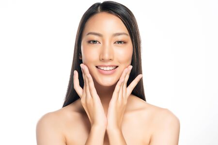 Beautiful Young Asian Woman with Clean Fresh Skin is touching her face