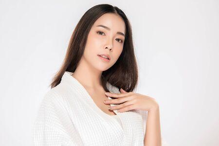 Hermosa joven asiática mirando mientras toca el hombro sintiéndose tan feliz y alegre con una piel sana y limpia y fresca, aislado sobre fondo blanco, concepto de belleza cosmetología,