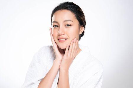 아름다운 젊은 아시아 여성이 부드러운 뺨을 만지고 깨끗하고 신선한 피부로 미소를 짓습니다. 행복과 명랑, 흰색 배경에 고립 된 아름다움과 화장품 개념,