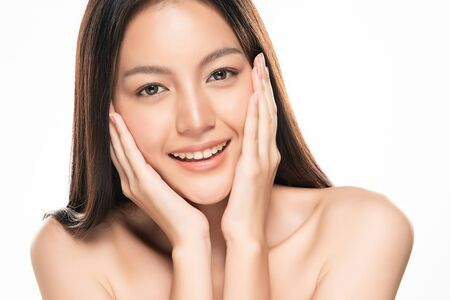 Mooie jonge Aziatische vrouw die zachte wang aanraakt en glimlacht met een schone en frisse huid. Geluk en vrolijk met, geïsoleerd op een witte achtergrond, Beauty en Cosmetics Concept,