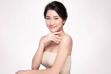 Hermosa joven asiática tocando la mejilla suave y una sonrisa con la piel limpia y fresca. Felicidad y alegría con, aislado sobre fondo blanco, concepto de belleza y cosméticos,