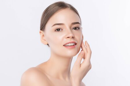 Beautiful Young Woman touching her clean face with fresh Healthy Skin, isolated on white background, Beauty Cosmetics and Facial treatment Concept. Standard-Bild