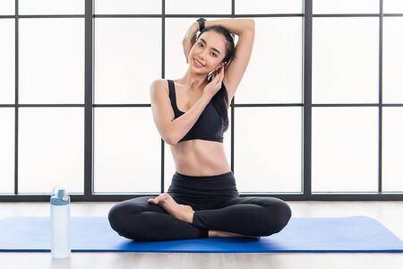 beautiful young  Asian Woman in is exercise on her yoga class. Working out in fitness studio.