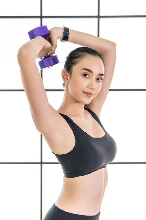 beautiful young Asian Woman in is exercise on class. Working out in fitness studio.