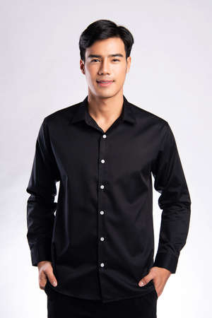 handsome confident young man standing and smiling in a back shirt. on white background.