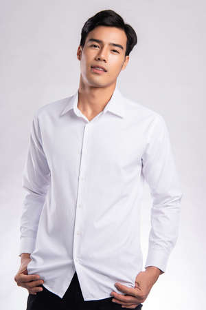 handsome confident young man standing and smiling in a white shirt. on white background.