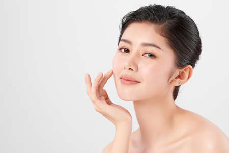 Beautiful young asian woman with clean fresh skin on beige background, Face care, Facial treatment, Cosmetology, beauty and spa, Asian women portrait. Stock Photo