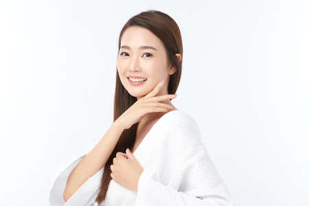 Beautiful young Asian woman wearing bathrobe on white background, Face care, Facial treatment, Cosmetology, beauty and spa Concept. Standard-Bild