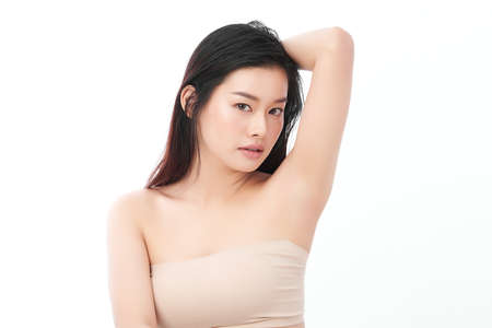 Beautiful Young Asian woman lifting hands up to show off clean and hygienic armpits or underarms on white background, Smooth armpit cleanliness and protection concept Stock fotó