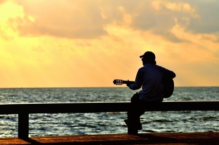 man met gitaar bij zonsondergang