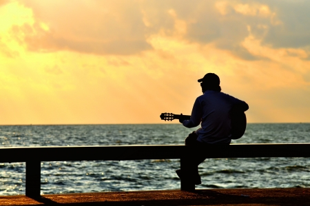 musician silhouette: man with guitar at sunset