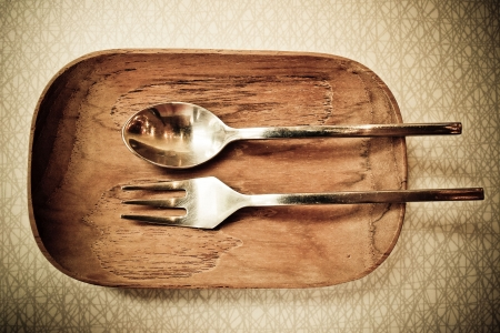 Stainless fork and spoon on wood plate