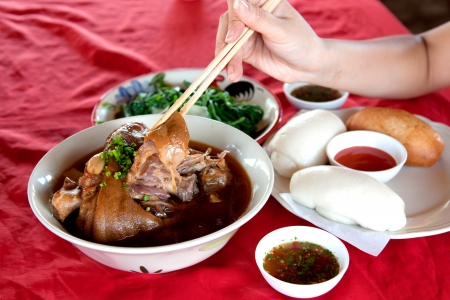 red tablecloth: Traditional Chinese food Stewed pork leg and Chinese steamed bun on red tablecloth. The high calorie. Stock Photo