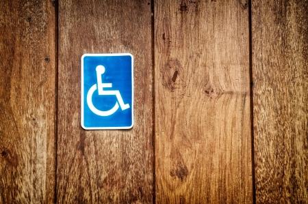 handicap sign: handicap sign on wooden background Stock Photo