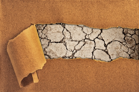 drought land and cracked ground behind torn paper photo