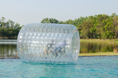 ball on water: Child enjoys rolling ball or zorbing air bubbles on water
