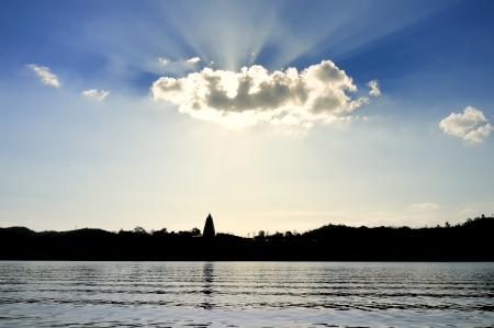 wiwekaram: Sun shining through clouds, Wat Wang Wiwekaram, Sangkhla Buri, Thailand Stock Photo