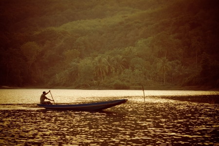 Silhouette of  fishermen in a small boat on a lake photo