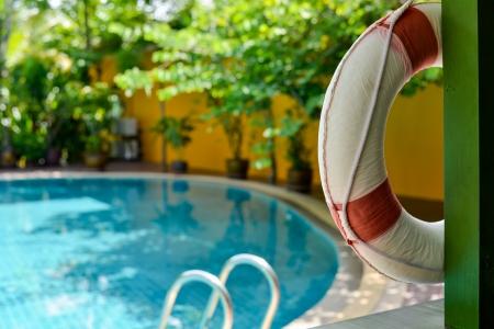 プールで木製の梁に掛かっている救命浮環