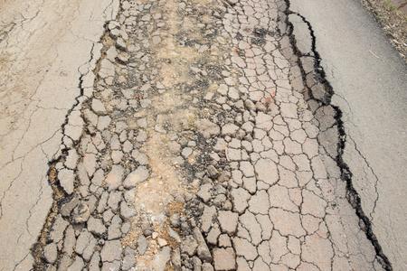 earthquake crack: Asphalt street cracked and broken