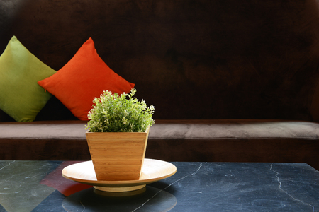 Small artificial  tree on the table with modern furniture