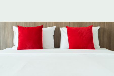 bed sheet: Red and white pillows on a bed Stock Photo