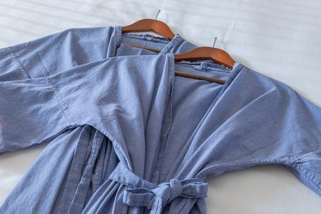 hotel bedroom: Clean blue bathrobe on comfortable bed