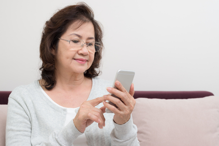 Happy Asian senior woman sitting on sofa and using a smart phone