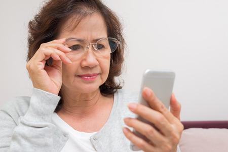 アジアの年配の女性は、彼女の電話で新しいメッセージに心配しています。