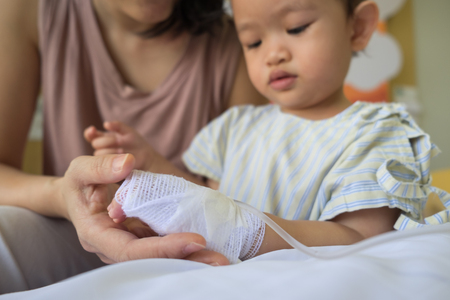 iv: mother holding childs hand receiving iv saline solution in hospital. Stock Photo