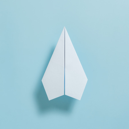 Flat lay of white paper plane on pastel blue color background