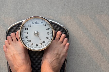 Close-up Feet Standing On Weighing Scale