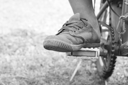 pedal: The boy foot on pedal of bicycle Stock Photo