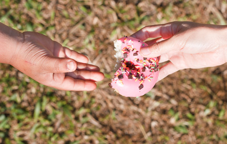 giving a donut to a child. photo