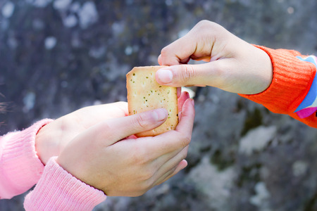 Sharing food. Women giving a cracker to a small child. Charity concept. photo
