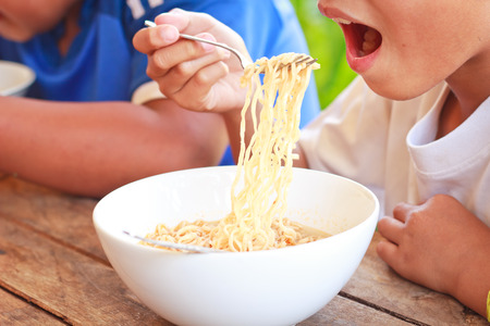 instant noodle: Children eating their  instant noodle in white bowl on wood table,Focused on instant noodle.
