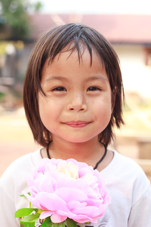 buoyant: Nongkhai, Thailand - March 16: Unidentified smiling child joyful to show her big flower in her hand at Phon Phisai Strawberry farm on Phonphisia in Nongkhai, Thailand on March 16, 2015.