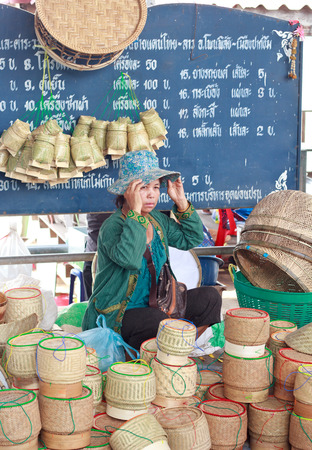basketry: Nongkhai, Thailand - May 016: Unidentified   shop seller at basketry shop wait customer to buy her goods at Thai-Laos vintage market on Phonphisia in Nongkhai, Thailand on May 16, 2015.