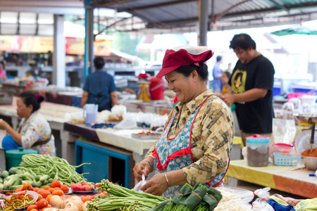 sales person: Nongkhai, Thailand - May 09, 2015: Unidentified smiling shop owner of vegetable shop packing her goods befor sell to customer at RATTANAWAPEE market on Phonphisia in Nongkhai, Thailand on May 09, 2015.