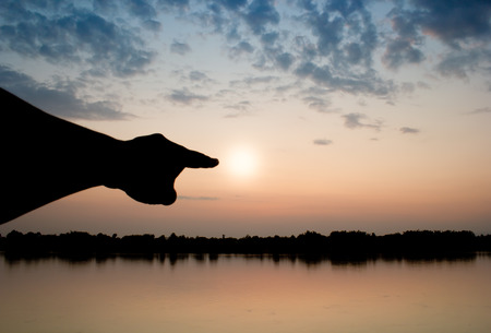 sun set: silhouette hand point to the sun in sun set. Stock Photo