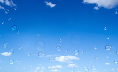 suds: Soap suds fly on blue sky background. Stock Photo