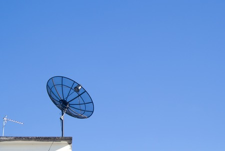 microwave antenna: Satellite dish transmission data with blue sky background. Stock Photo