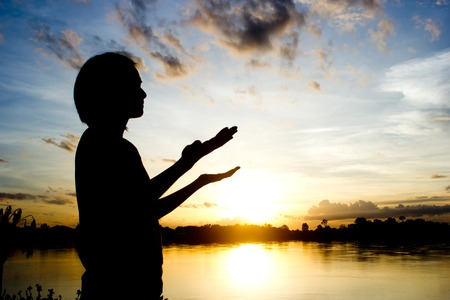 orando: siluetas de mujeres rezando mano sobre hermoso fondo puesta de sol.